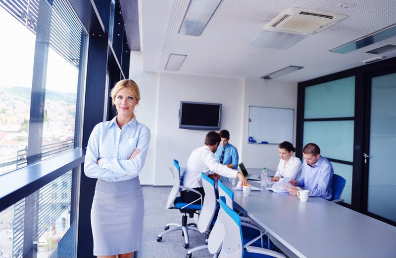 A businesswoman stands in a conference room with her team.