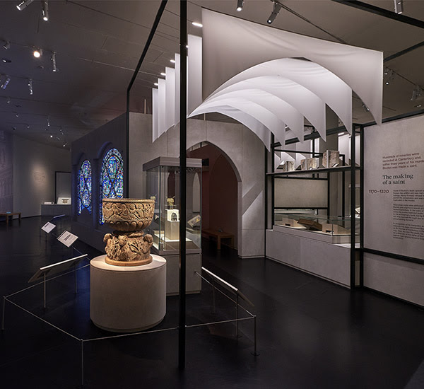 Inside 'Thomas Becket: murder and the making of a saint' showing stained glass, a stone font, and other objects on display. Hanging drapes form the shape of an arched corridor.