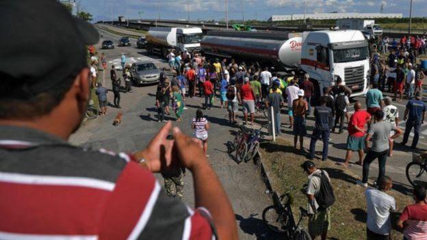Em foto de 2018, homem observa dezenas de manifestantes em volta de caminhão parado em estrada do Rio