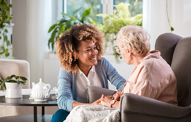 A caregiver assisting a senior woman in her home.