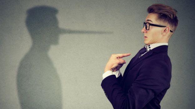 Homem apontando a si mesmo em frente a sombra que remete ao personagem pinóquio