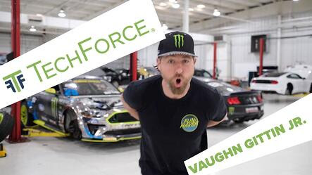 "Video thumbnail for Vaughn Gittin, Jr.'s shout-out for TechForce's peer network. Vaughn is standing in a well-lit, white autoshop with racecars behind him. The words ""TechForce"" and ""Vaughn Gittin, Jr."" appear in green letters over white boxes on screen."