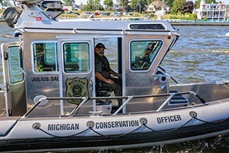 Corporal Ivan Perez is pictured operating a DNR law enforcement boat.
