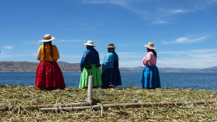 Uros women waiting for their guests to arrive on one of the floating islands, Lake Titicaca, Peru