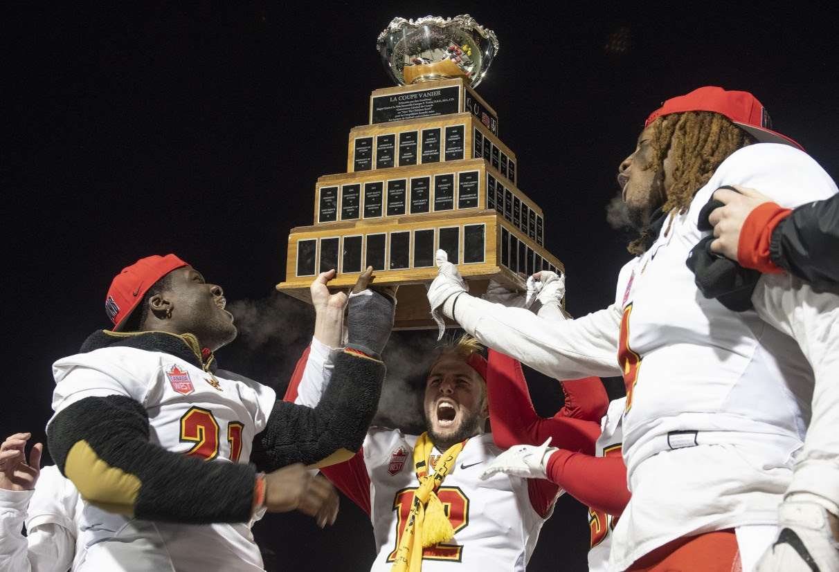 Calgary Dinos players hold up the Vanier Cup (Canadian Press)