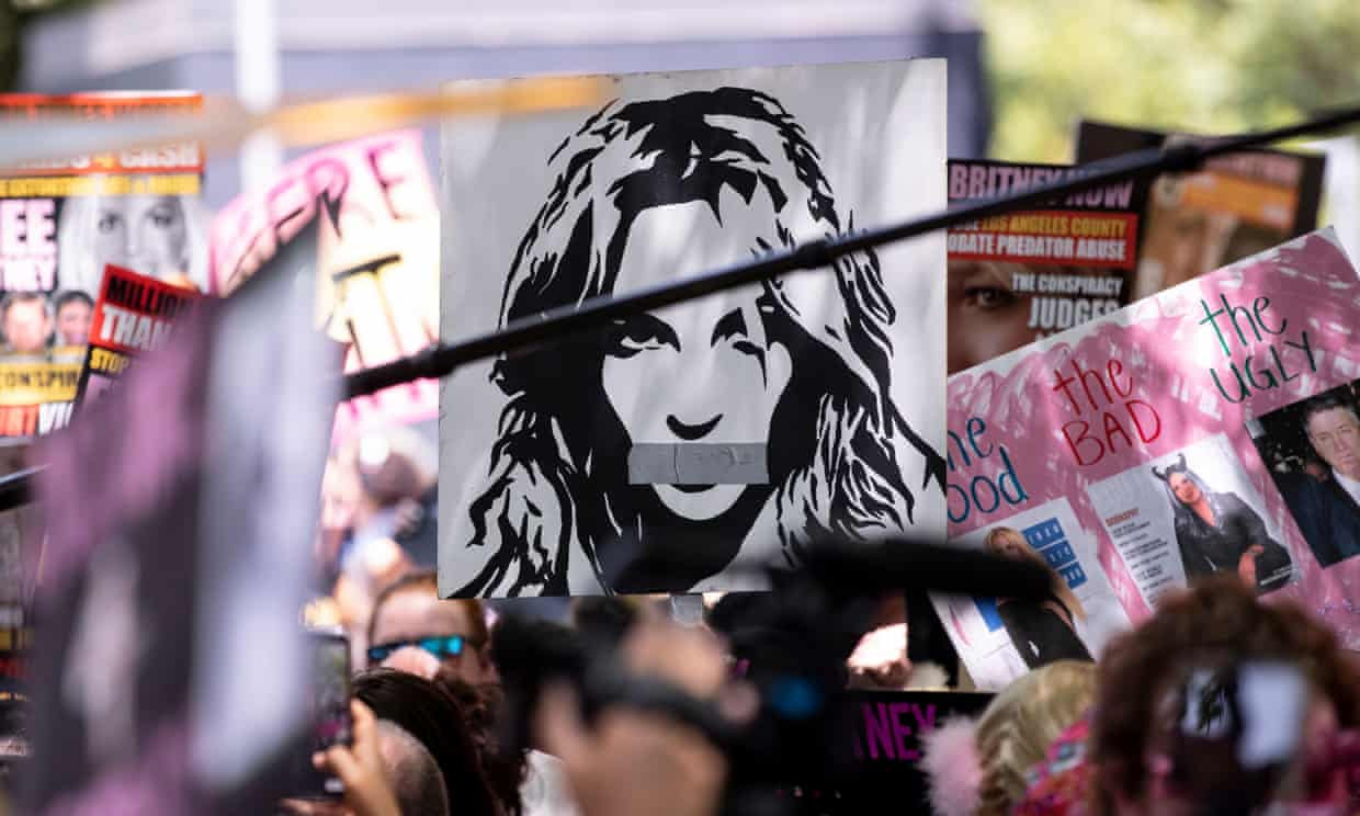 A protest with a sign with Britney Spears with her mouth taped closed
