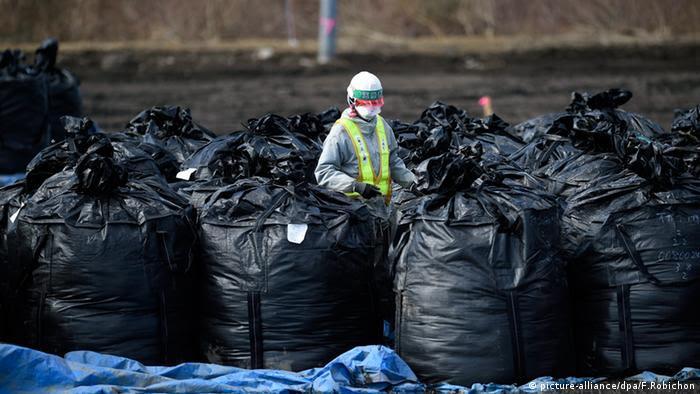 Trabalhador de roupa protetora em meio a sacos de lixo cheios