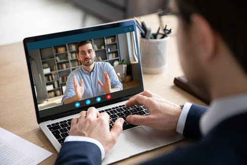 Back view of businessman talk with male business partner using video call on laptop discuss work project online_ male client talk with colleague or coworker_ speak on webcam conference on computer