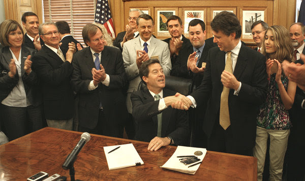 Gov. Sam Brownback, center, signed the tax bill into law in May 2012. The law cut individual income taxes and eliminated state income taxes entirely for pass-through entities in an attempt to attract investment and create jobs.