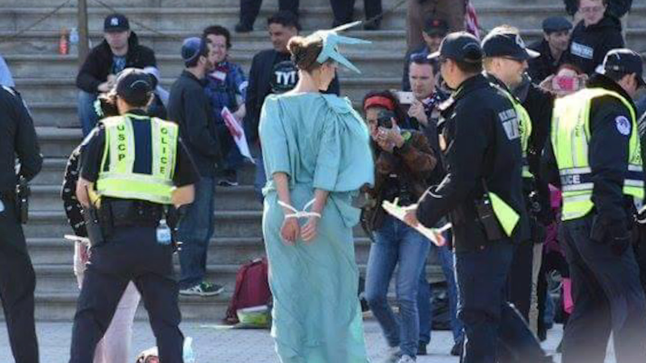 Person in Statue of Liberty costume cuffed by police