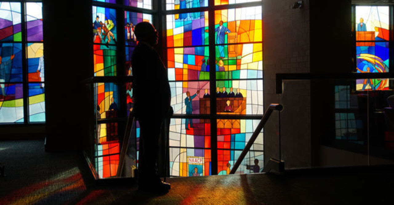 Henry Louis Gates Jr. standing in front of stained glass