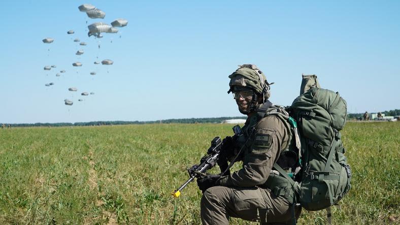 Izraelski żołnierz zajmujący pozycję, w tle desant powietrzny izraelskich spadochroniarzy