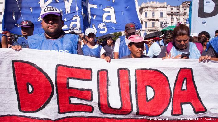 Manifestantes atrás de grande faixa com a palavra deuda (dívida em espanhol)