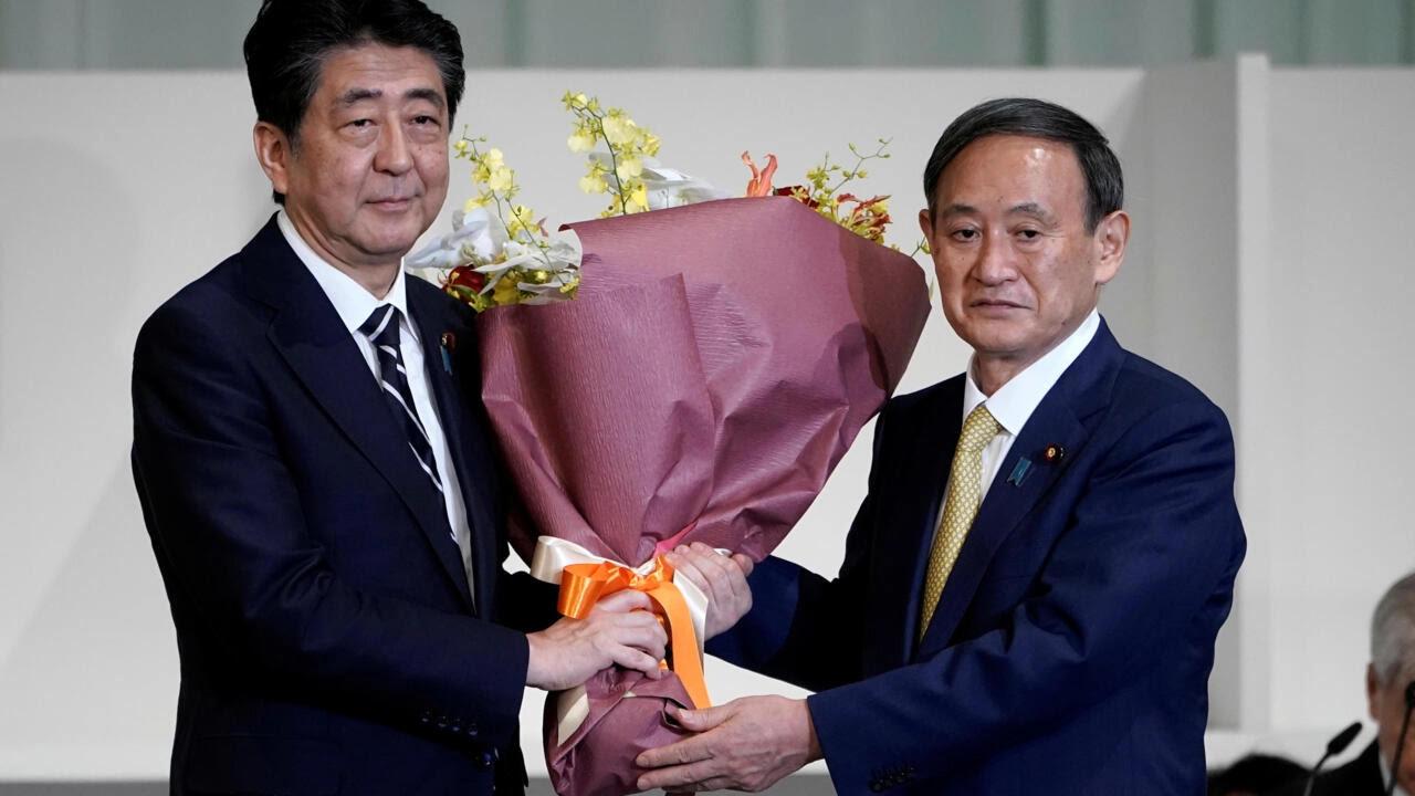 Thủ tướng Nhật Bản đã từ nhiệm Shinzo Abe (T) tặng hoa cho chánh văn phòng nội các Yoshihide Suga sau khi nhân vật này được bầu làm lãnh đạo mới của đảng Dân Chủ Tự Do (LDP) ở Tokyo, Nhật Bản ngày 14/09/2020.