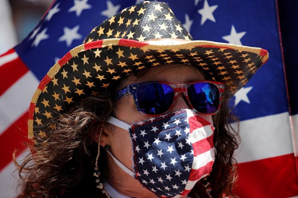 Un manifestante con una máscarilla con los colores de la bandera de EEUU en una protesta contra el cierre de actividad y de negocios decretado por la pandemia del coronavirus, en Los Ángeles (California, EEUU). REUTERS / Mike Blake