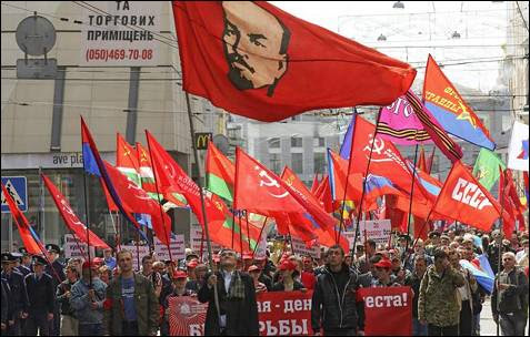 Un simpatizante del Partido Comunista ucraniano con un retrato de Lenin al fondo, durante la celebración del 'Primero de Mayo' en Kharkiv, Ucrania.
