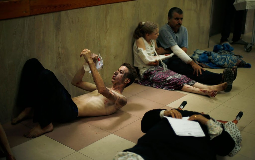 Palestinians, who medics said were wounded during heavy Israeli shelling, sit at a hospital in Gaza City July 20, 2014.  REUTERS/Mohammed Salem