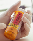 Gloved hand pointing at drug bottle label