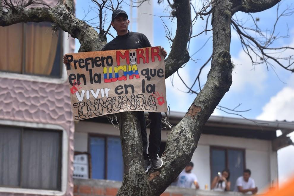 01/05/2021. Un hombre sostiene un cartel en nueva jornada de protesta contra la reforma tributaria defendida por el presidente de Colombia. - EFE