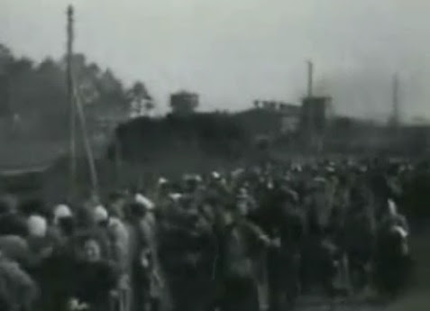 German prisoners of war in a queue                             (11min. 6sec.), many have white bandages on                             their head because of head injuries