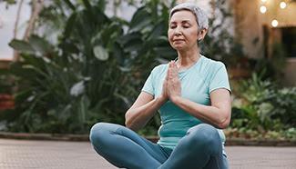 Grey haired woman sitting in lotus pose meditating