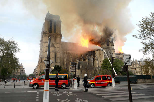 Slide 17 of 31: PARIS, FRANCE - APRIL 15:  Flames and smoke are seen billowing from the roof at Notre-Dame Cathedral April 15, 2019 in Paris, France. A fire broke out on Monday afternoon and quickly spread across the building, collapsing the spire. The cause is yet unknown but officials said it was possibly linked to ongoing renovation work. (Photo by Pierre Suu/Getty Images)