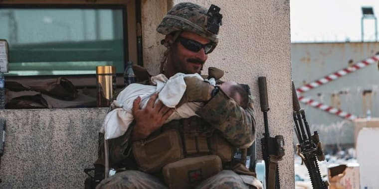 Image: A U.S. Marine assigned to the 24th Marine Expeditionary Unit (MEU) holds a baby during an evacuation at Hamid Karzai International Airport, Kabul