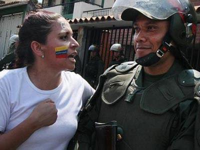 Una manifestante opositora junto a un miembro de las Fuerzas Armadas.