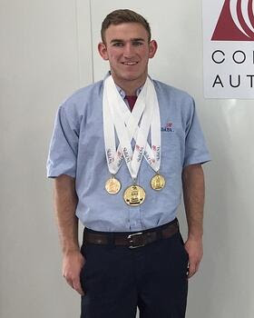 Ben Falconer standing in front of a white wall, wearing several gold medals on white ribbons around his next.
