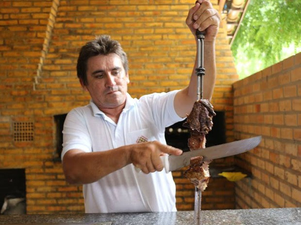 Churrasqueiro realiza o corte da carne de jumento para servir (Foto: Marcelino Neto/G1)