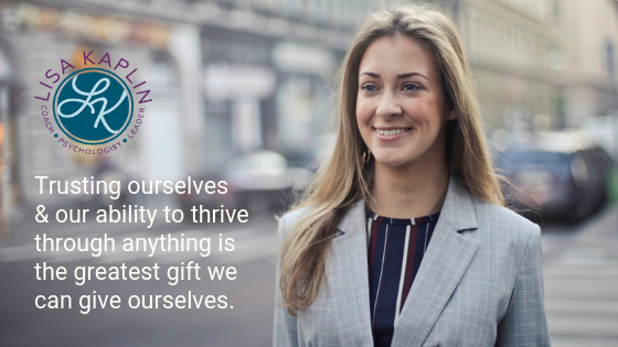 "A color photo of a white woman in a business suit smiling while walking down a city streets. In the top left corner of the photo is the text ""Trusting ourselves and our ability to thrive through anything is the greatest gift we can give ourselves."" The Lisa Kaplin logo is above the text."
