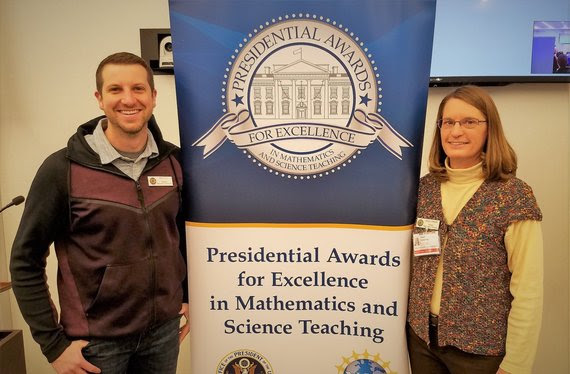 "The WDE math and science standards consultants stand on either side of a banner with reads, ""Presidential Awards for Excellence in Mathematics and Science Teaching."""