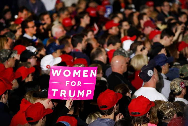 "A supporter holds a ""Women For Trump"" poster during the president's rally last month in Washington Township, Mich., which is part of Macomb County. (Paul Sancya/AP)"