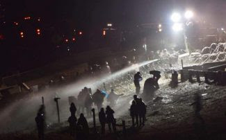 Water Protectors sprayed with water in freezing weather on November 20th