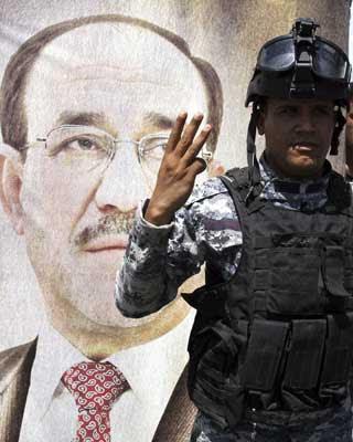n soldado iraquí muestra tres dedos haciendo referencia a un tercer mandato de Nuri al Maliki en Bagdad.
