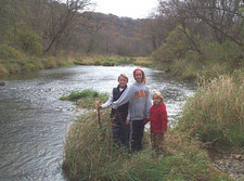 three kids standing on a stream bank island in grass during a hike