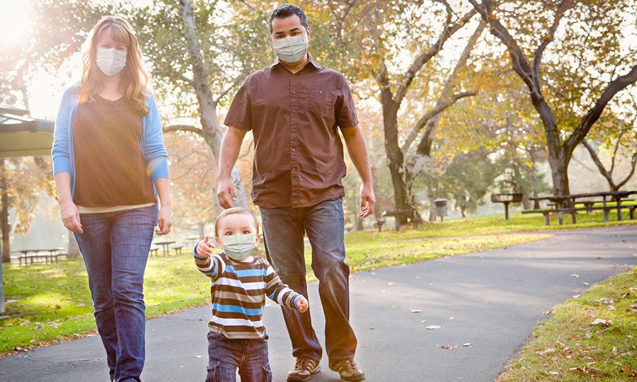 una pareja joven y su niño caminando en un parque. Los tres llevan máscaras