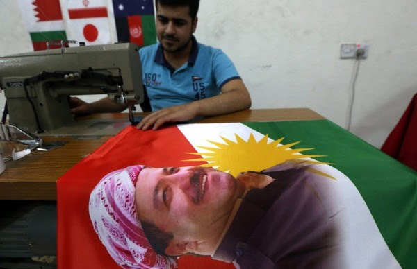 An Iraqi man sews a flag of Kurdistan bearing the portrait of Masoud Barzani in Irbil on June 8. (Safin Hamed/Agence France-Presse via Getty Images)