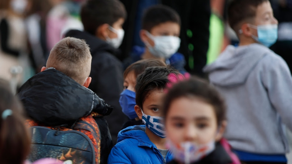 A young student wearing a face mask with the Greek flag, waits to enter his classroom at a primary school in Athens. Primary schools and kindergartens in Greece reopened have as the country has extended a two-month lockdown to curb the spread of the coronavirus, Jan. 11, 2021.