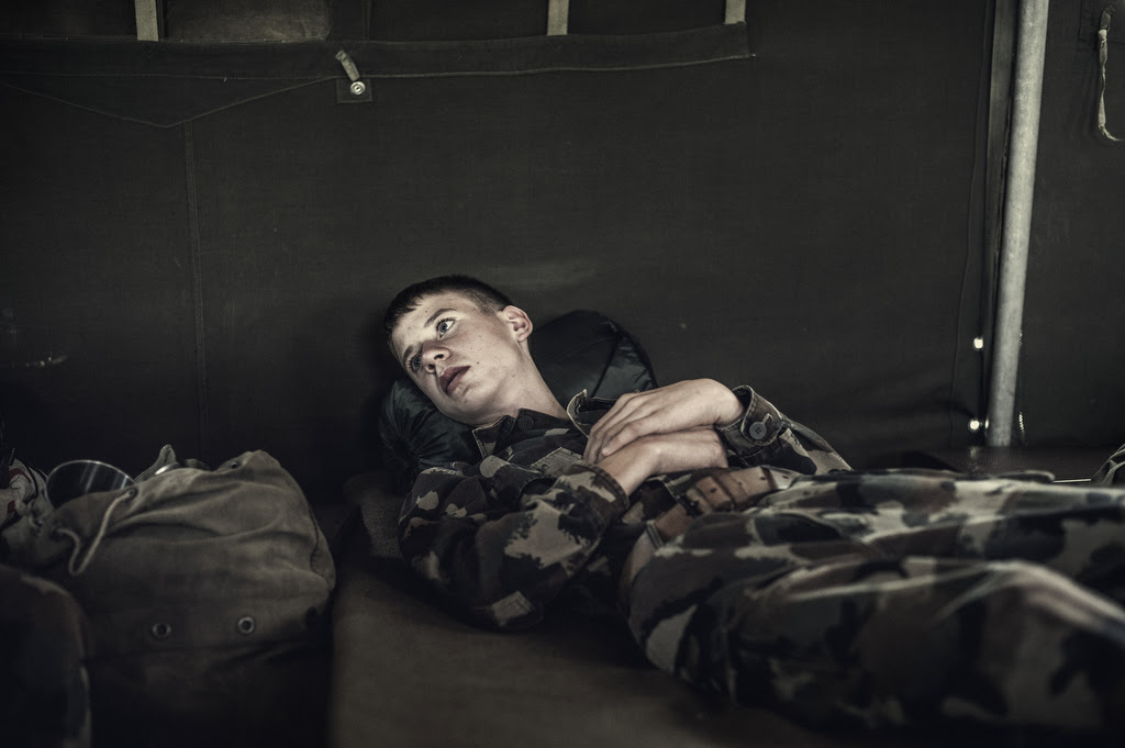 Photo: One of the youths attending the military, thoughtful, during one of the few moments of rest in one of the military tents where children sleep during the week-long summer military camp. The obvious vulnerability of some young people contrasts with the empowerment that comes with military lifestyle to most of the guys. During the week they will be assigned an uncomfortable bed, a stool, and a set of fork and spoon which should care for and maintain order. © Oriol Segon Torra.