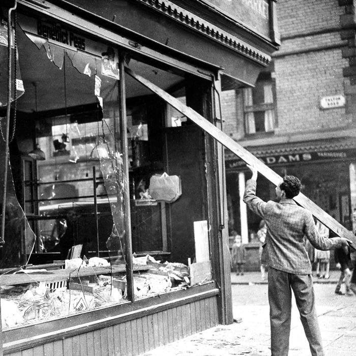 A workman knocks down the hanging glass in a shop window, Aug. 5, 1947, in Liverpool, England, which was damaged during anti-Semitic riots. Incidents have flared in many British cities and more than a score of demonstrators have been arrested in Liverpool. (AP Photo)