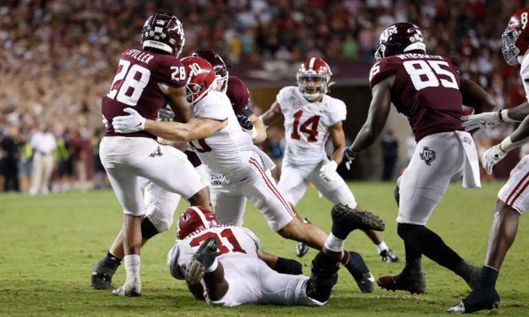 Henry To'oto'o (#10) and Will Anderson (#31) for Alabama tackling Texas A&M running back Isaiah Spiller