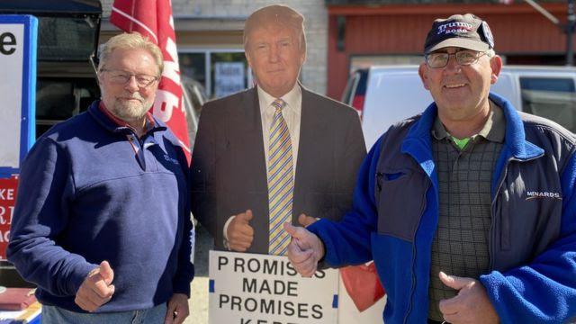 Dois homens em West Bend, no Condado de Washington, com uma placa de Trump