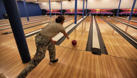 Una soldado juega en la bolera en la base naval de Guantánamo. Algunas personas llevan bolsas de diseño militar para transportar sus bolos. La bolera está al lado de un gimnasio y de un campo de fútbol americano.