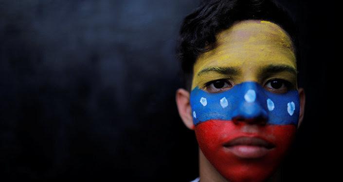 Un ciudadano con la bandera de Venezuela en su cara