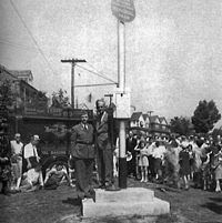 A man in a suit standing on a stage next to a large pole. There is a Marine in the background in his dress uniform and behind him a crowd of people are watching the man on the stage.