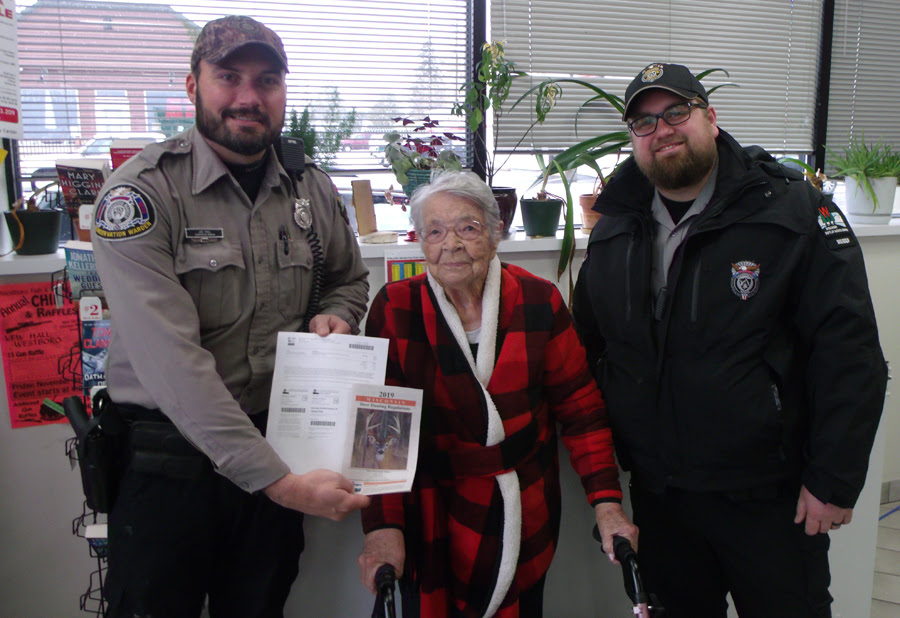 Florence Teeters poses with DNR Wardens after buying her first gun deer license.  -  - Photo credit: Bill Ball