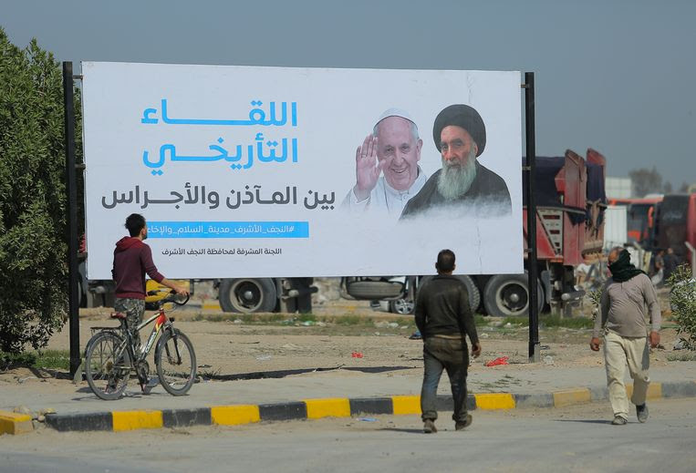 Een billboard kondigt de komst van paus Franciscus naar Najaf aan. Beeld AP