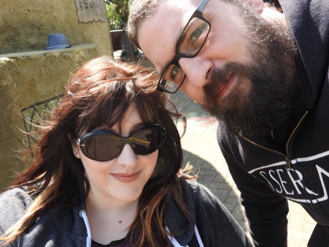 A woman and a man outdoors. The woman wears sunglasses and has long brown hair and the man wears black glasses and has a full beard