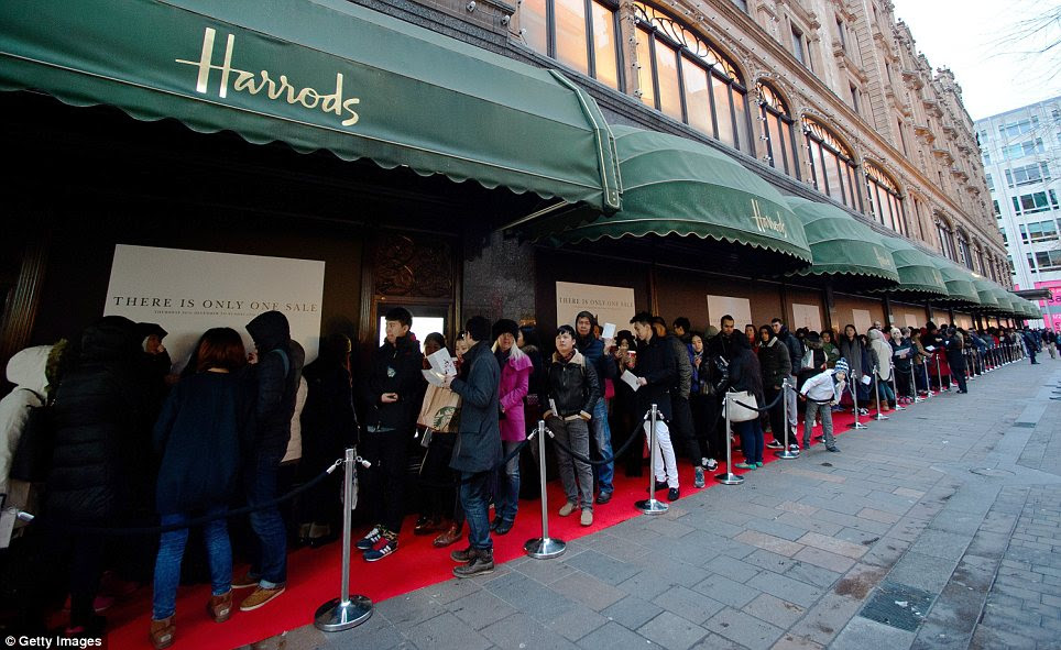 Getting ready: Shoppers queuing outside Harrods in Knightsbridge, where dozens of butlers are set to help customers